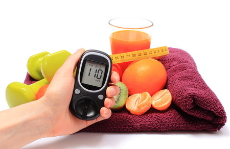 strengthening: Hand with glucose meter, fresh fruits with tape measure, glass of juice and green dumbbells for fitness, concept for diabetes, slimming, healthy nutrition and strengthening immunity