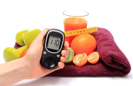 diabetes: Mano con medidor de glucosa, frutas frescas con cinta métrica, vaso de jugo y mancuernas verdes para la aptitud, el concepto de la diabetes, de adelgazamiento, la alimentación sana y el fortalecimiento de la inmunidad