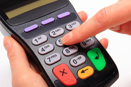 Hand of woman using payment terminal, enter personal identification number, finance concept photo