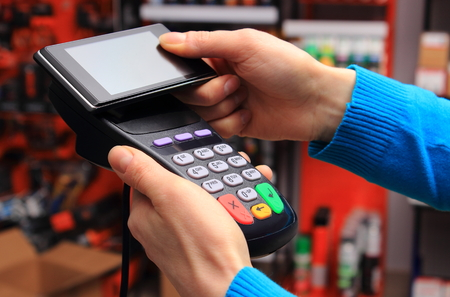 mobile phone: Hand of woman paying with NFC technology on mobile phone in an electrical shop, credit card reader, payment terminal, finance concept Stock Photo