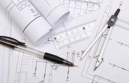 paper and pen: Rolled electrical diagrams and accessories for drawing lying on construction drawing of house, drawings and accessories for the projects engineer jobs