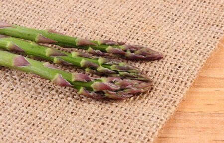 inmunidad: Esp�rrago verde fresco en la bolsa de arpillera, el concepto de la comida sana, la nutrici�n y el fortalecimiento de la inmunidad. Fondo de madera