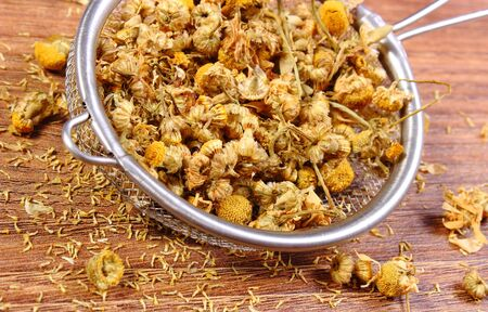 herbalism: Heap of dried chamomile on metal sieve lying on wooden surface, concept of healthy nutrition, herbalism and alternative medicine