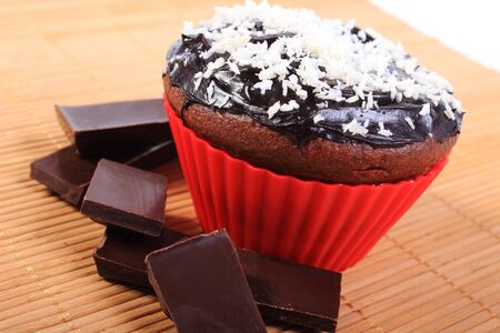 desiccated: Homemade delicious fresh baked chocolate muffins with desiccated coconut in red silicone cups and pieces of chocolate, concept for dessert