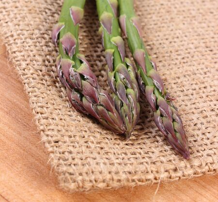 immunity: Fresh green asparagus on burlap bag, concept of healthy food, nutrition and strengthening immunity. Wooden background