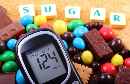 diabetes: Medidor de glucosa con azúcar palabra, montón de caramelos, galletas y azúcar de caña marrón, demasiados dulces, comida poco saludable, el concepto de la diabetes y la reducción de comer dulces