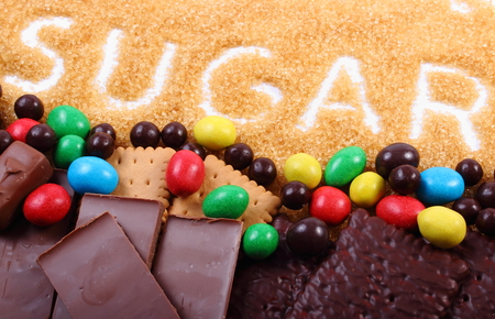 too many: Word sugar written in granulated natural brown cane sugar and a lot of candies and cookies, concept of too many sweets and unhealthy food Stock Photo