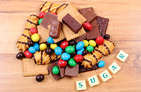 too many: Heap of candies and cookies with word sugar on wooden table, too many sweets, concept of unhealthy food and reduction of eating sweets