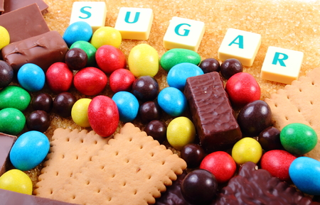 brown sugar: Heap of sweet candies and cookies with brown cane sugar and word sugar, unhealthy food, reduction of eating sweets Stock Photo