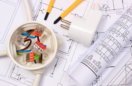 Copper wire connections in electrical box, rolls of electrical diagrams and electric plug on construction drawing of house, accessories for engineering work, energy concept Stockfoto