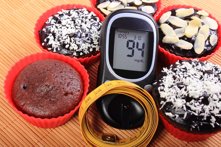 diabetes: Glucose meter, homemade delicious fresh baked chocolate muffins in red silicone cups and tape measure, concept for diabetes, slimming and dessert