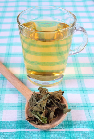 sedative: Healthy dried lemon balm with wooden spoon and glass of calming herbal drink on tablecloth, sedative herbs, concept for healthy nutrition and herbalism