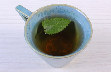 herbalism: Leaf of green lemon balm in cup of calming herbal drink on white wooden table, sedative herbs, concept for healthy nutrition and herbalism