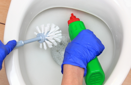 Hand of woman in blue glove cleaning toilet bowl using brush and detergent, concept for house cleaning and household duties