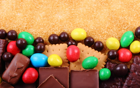 sweet food: A lot of candies and cookies with brown cane sugar, too many sweets, unhealthy food, reduction of eating sweets Stock Photo