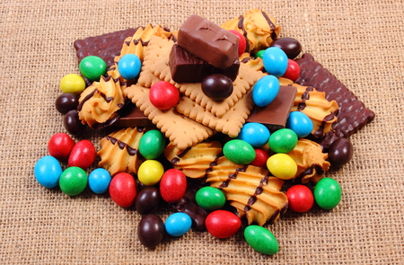 Heap of candies and cookies on jute burlap, too many sweets, concept of unhealthy food and reduction of eating sweets