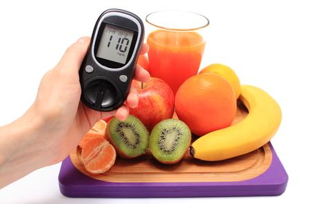 diabetes: Mano con glucómetro, frutas naturales frescas maduras y vaso de jugo en la tabla de cortar, el concepto de la diabetes, la nutrición saludable y el fortalecimiento de la inmunidad