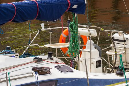 coiled rope: Yachting, parts of sailboat in port of sailing, coiled rope, sail and orange lifebuoy, details of yacht Stock Photo