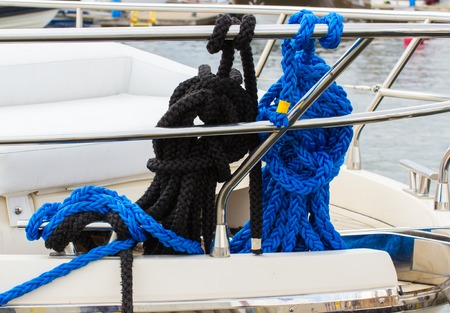 coiled rope: Yachting, coiled black and blue rope on deck of sailboat, details and part of yacht Stock Photo