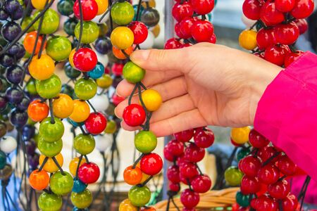 womanly: Looking at wooden colorful necklace, shopping jewelry and womanly accessories on stall at the bazaar Stock Photo
