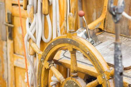 helm: Yachting, helm of old wooden sailboat in port of sailing, rope, steering wheel, details of yacht Stock Photo