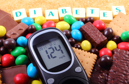 Glucose meter with word diabetes, heap of candies, cookies and brown cane sugar, too many sweets, unhealthy food, concept of diabetes and reduction of eating sweets Stockfoto