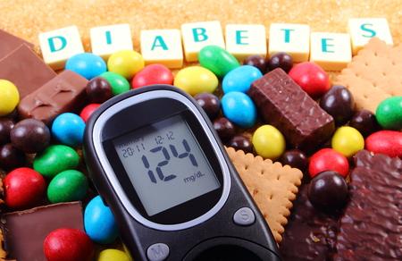 diabetes: Medidor de glucosa en la diabetes de palabras, montón de caramelos, galletas y azúcar de caña marrón, demasiados dulces, comida poco saludable, el concepto de la diabetes y la reducción de comer dulces Foto de archivo