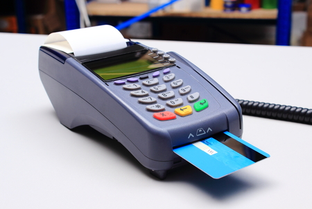 credit card reader: Payment terminal with credit card on desk in store, credit card reader, payment terminal, finance concept