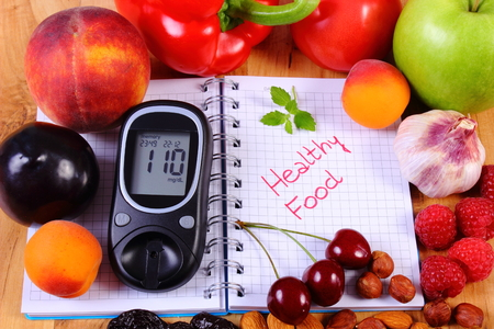 Fresh fruits, vegetables and glucose meter on notebook for writing notes, concept of healthy nutrition, diet and diabetes, sugar level
