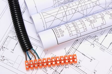 electrical component: Corrugated pipe, electrical cable with connection cube and rolls of electrical diagrams on construction drawing, accessories for engineering work Stock Photo