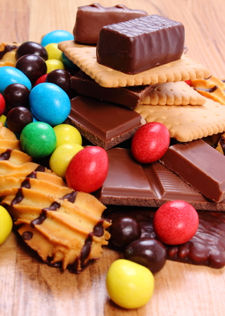 sweet food: Heap of candies and cookies on wooden table Stock Photo