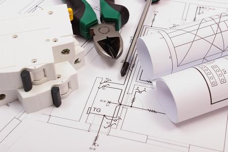 ingenieria elÉctrica: Pinzas de metal, destornillador, fusibles eléctricos y rollos de diagramas de dibujo de construcción eléctrica de la casa, herramienta de trabajo y de dibujo para los trabajos de proyectos de ingeniería Foto de archivo
