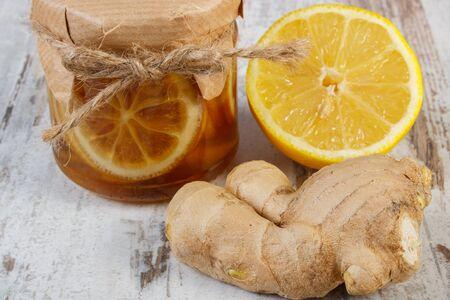 inmunidad: Lim�n con miel en frasco de vidrio, lim�n y jengibre en mesa de madera vieja, el concepto de la comida sana, la nutrici�n, el fortalecimiento de la inmunidad y la terapia alternativa
