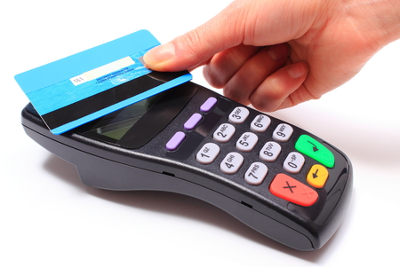 Hand of woman paying with contactless credit card with NFC technology, credit card reader, payment terminal, finance concept