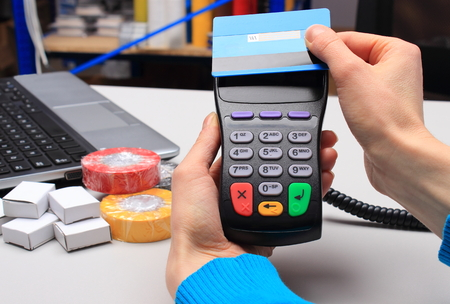 computer devices: Hand of woman paying with contactless credit card with NFC technology in an electrical shop, credit card reader, payment terminal, finance concept Stock Photo