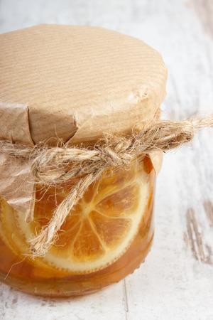 inmunidad: Lim�n con miel en frasco de vidrio tirado en mesa de madera vieja blanco, el concepto de la comida sana, la nutrici�n y el fortalecimiento de la inmunidad Foto de archivo