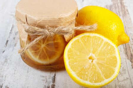 immunity: Lemon with honey in glass jar and fresh lemon on old wooden white table, concept of healthy food, nutrition and strengthening immunity Stock Photo