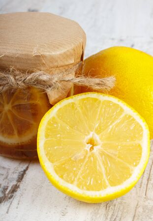 inmunidad: Lemon with honey in glass jar and fresh lemon on old wooden white table, concept of healthy food, nutrition and strengthening immunity Foto de archivo