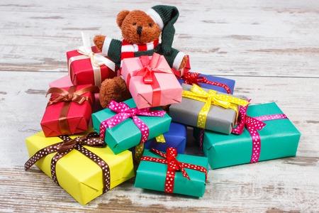 oso de peluche: Oso de peluche mullido y el montón de regalos coloridos envueltos para Navidad, cumpleaños, San Valentín o la otra celebración en la vieja mesa de madera blanca