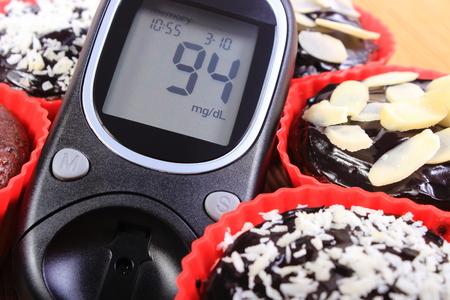 diabetes: Medidor de glucosa y caseras deliciosas magdalenas de chocolate al horno frescos en tazas de silicona de color rojo, el concepto de la diabetes y el postre