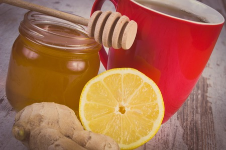 warming therapy: Vintage photo, Fresh lemon, honey in glass jar, ginger and cup of hot tea on old wooden white table, healthy food, strengthening immunity and alternative therapy Stock Photo