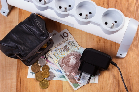 power of money: Electrical power strip with disconnected plug and polish currency money with black leather pocket purse, concept of saving money on electricity