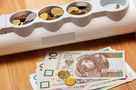 power of money: Electrical power strip and polish currency on wooden floor, power board, concept of saving money on electricity, energy costs