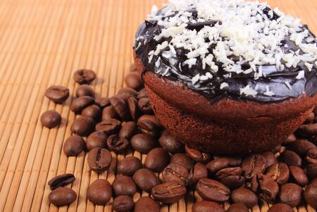 desiccated: Homemade delicious fresh baked chocolate muffins with desiccated coconut and coffee grains on wooden background, concept for dessert Stock Photo