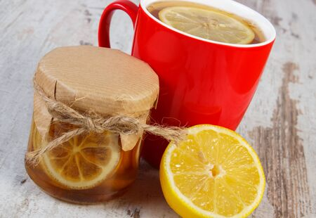 Lemon with honey in glass jar, fresh lemon and cup of hot tea on old wooden white table, healthy food, strengthening immunity and alternative therapy