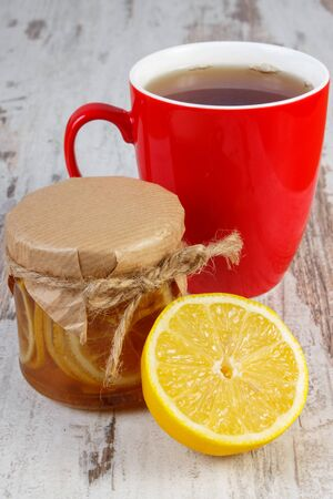 warming therapy: Lemon with honey in glass jar, fresh lemon and cup of hot tea on old wooden white table, healthy food, strengthening immunity and alternative therapy
