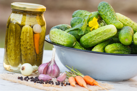 pickling: Ripe cucumbers in metal bowl, vegetables and spices for pickling and jar marinated cucumbers on old wooden white table in garden on sunny day