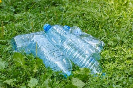 botar basura: Las botellas de pl�stico de agua mineral en la hierba en el parque, el concepto de protecci�n del medio ambiente, tirar basura del entorno Foto de archivo