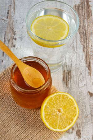 lemon water: Fresh lemon with honey and full glass of clean water with slice of lemon on old wooden white table, healthy beverage