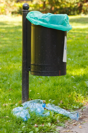 littering: Old trash can in park and heap of plastic bottles, concept of environmental protection, littering of environmental
